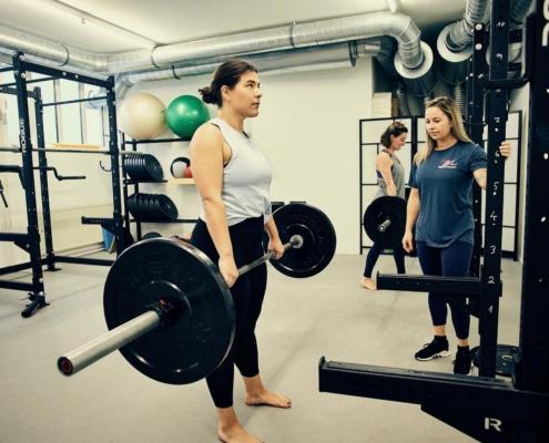 Trainerin Tessa hilft Kundin bei Gruppentraining in Wien an. optimumtraining.at