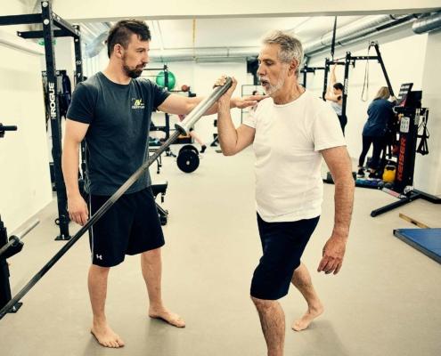 Trainer Sascha leitet Kundin bei Personal Training in Wien an. optimumtraining.at