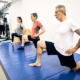 Drei Personen auf einer Matte trainieren ihre Beweglichkeit und Mobility. optimumtraining.at