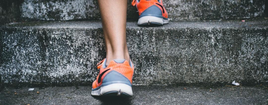 Ausschnitt von Treppen und einer Frau, die mit ihren Sportschuhen hinaufgeht. optimumtraining.at