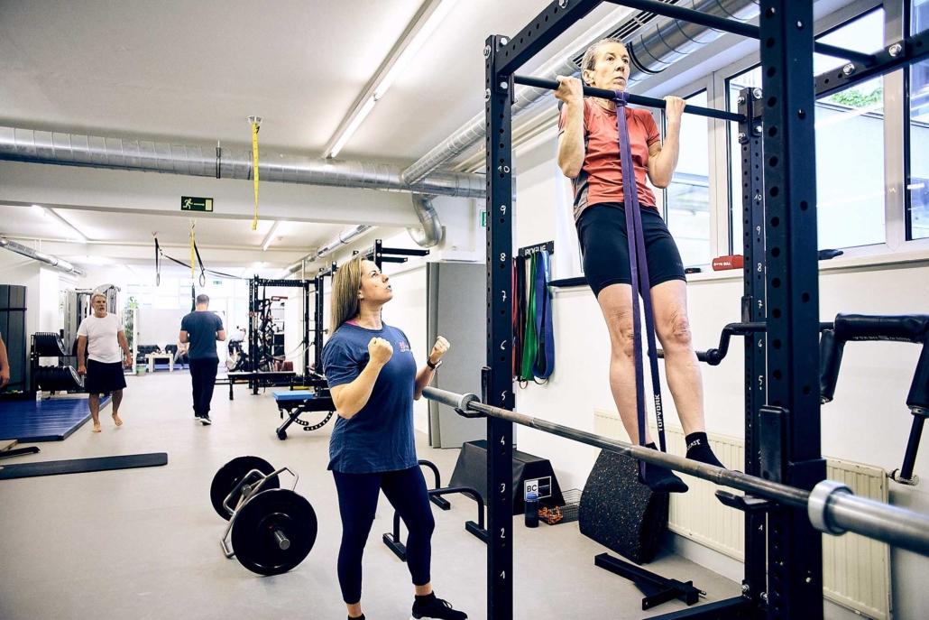 Trainerin Tessa motiviert bei Personal Training Frau beim Klimmzug machen. optimumtraining.at