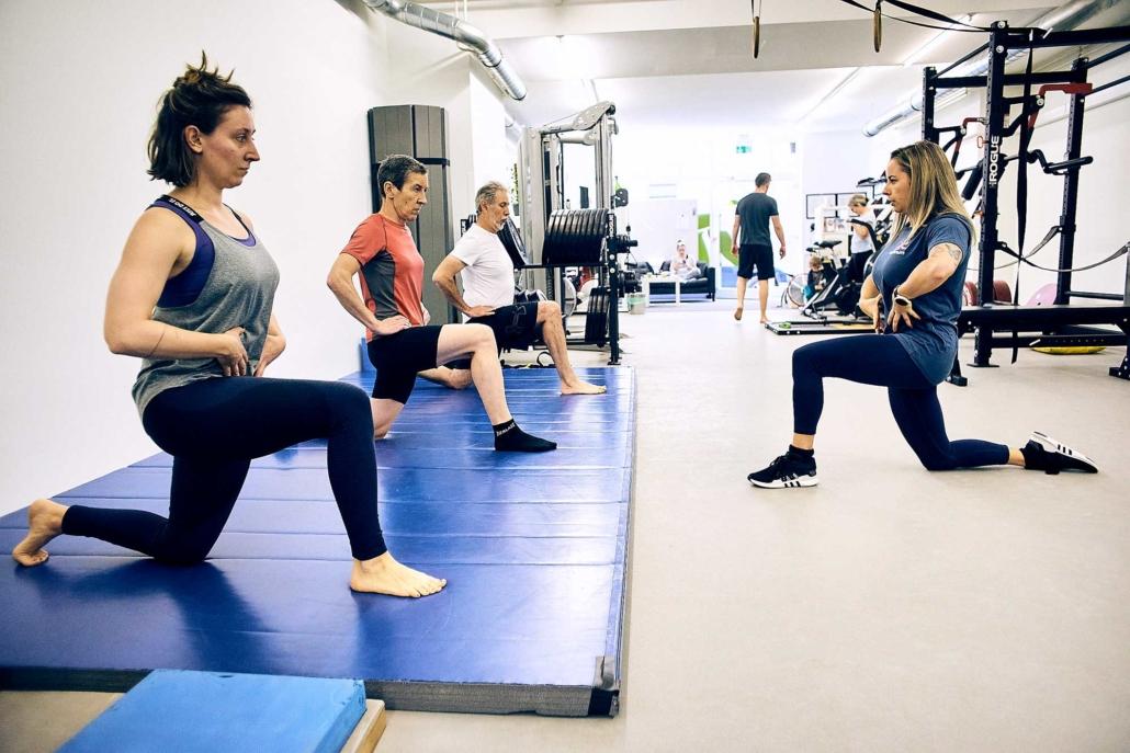 Trainerin Tessa zeigt beim Gruppentraining in Wien eine Übung vor. optimumtraining.at