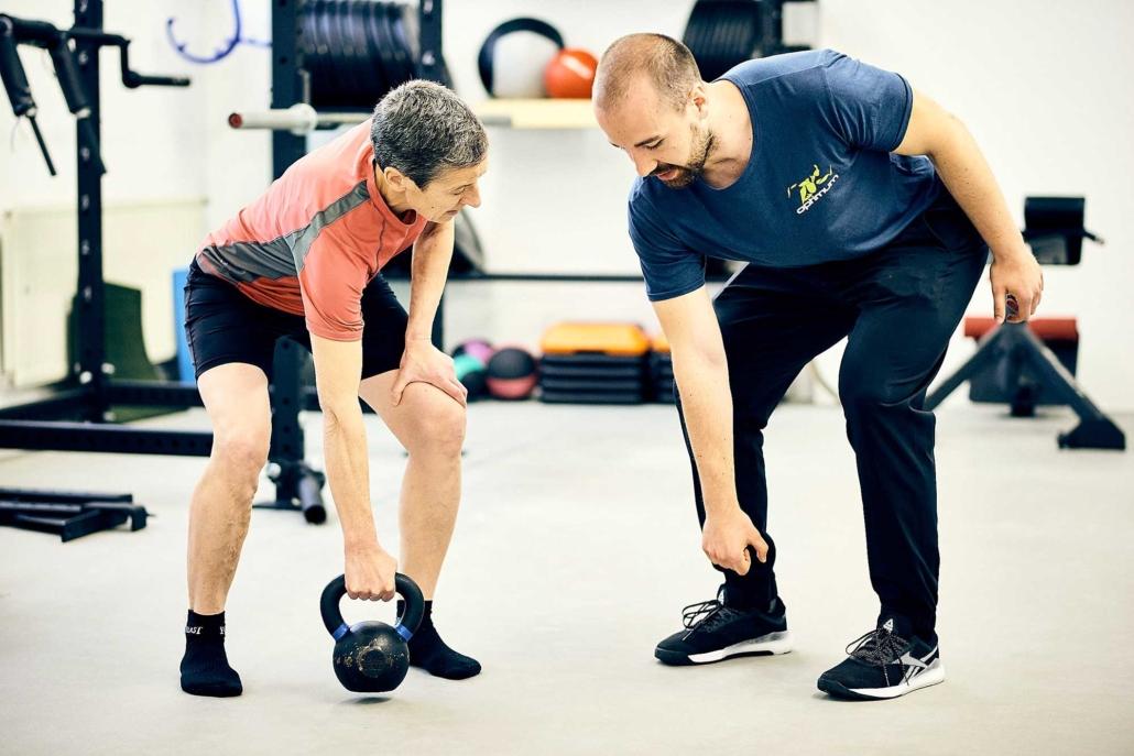 Trainer Paul zeigt bei Personal Training für Frauen eine Übung mit der Kettlebell vor. optimumtraining.at