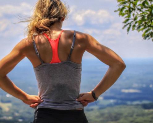 Frau stet auf Hügel und überblickt Landschaft. optimumtraining.at