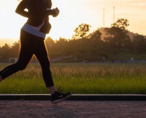 Frau mit Handy läuft in Park. Sonnenuntergang. optimumtraining.at