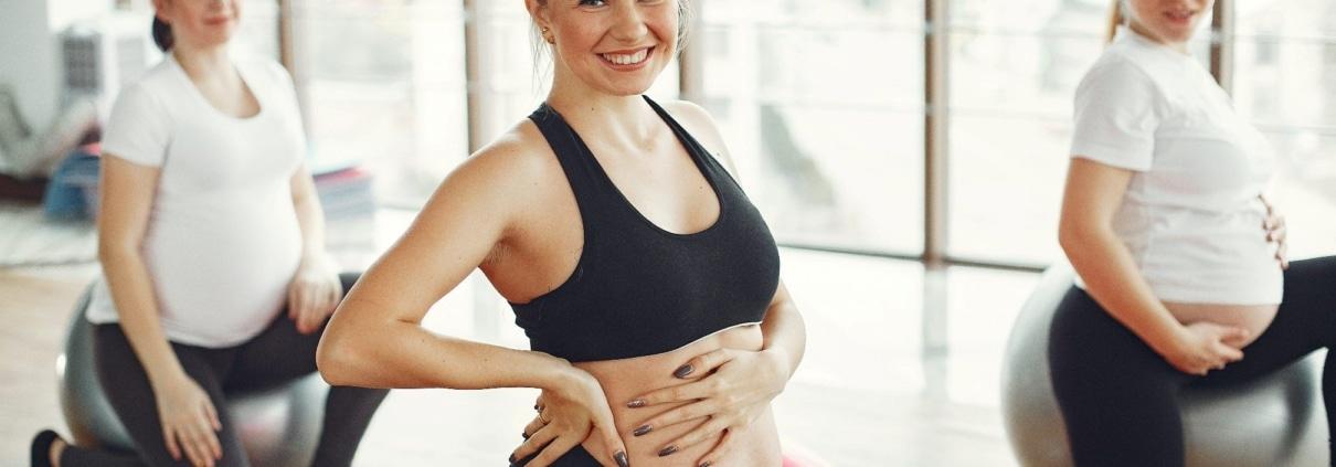 Schwangere Frau sitzt auf Gymnastikball und macht Sport. Sie greift sich dabei an den Babybauch. optimumtraining.at