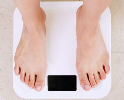 Füße stehen auf Körperwaage für Gewichtsverlust. optimumtraining.at